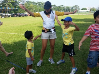Me faking jumping jacks with the kids at their sports day