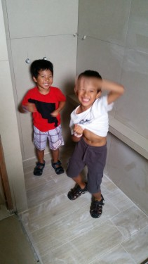 Funny boys pretending to bathe in the shower area