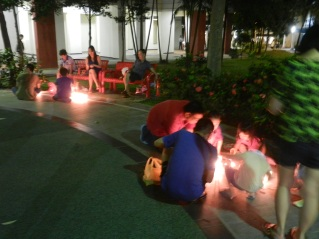 Friends and strangers gathering around to play with candles