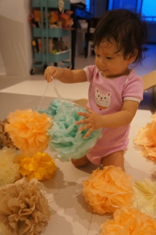 Playing with the pom poms the day after in her brand new cat romper that she got as a present